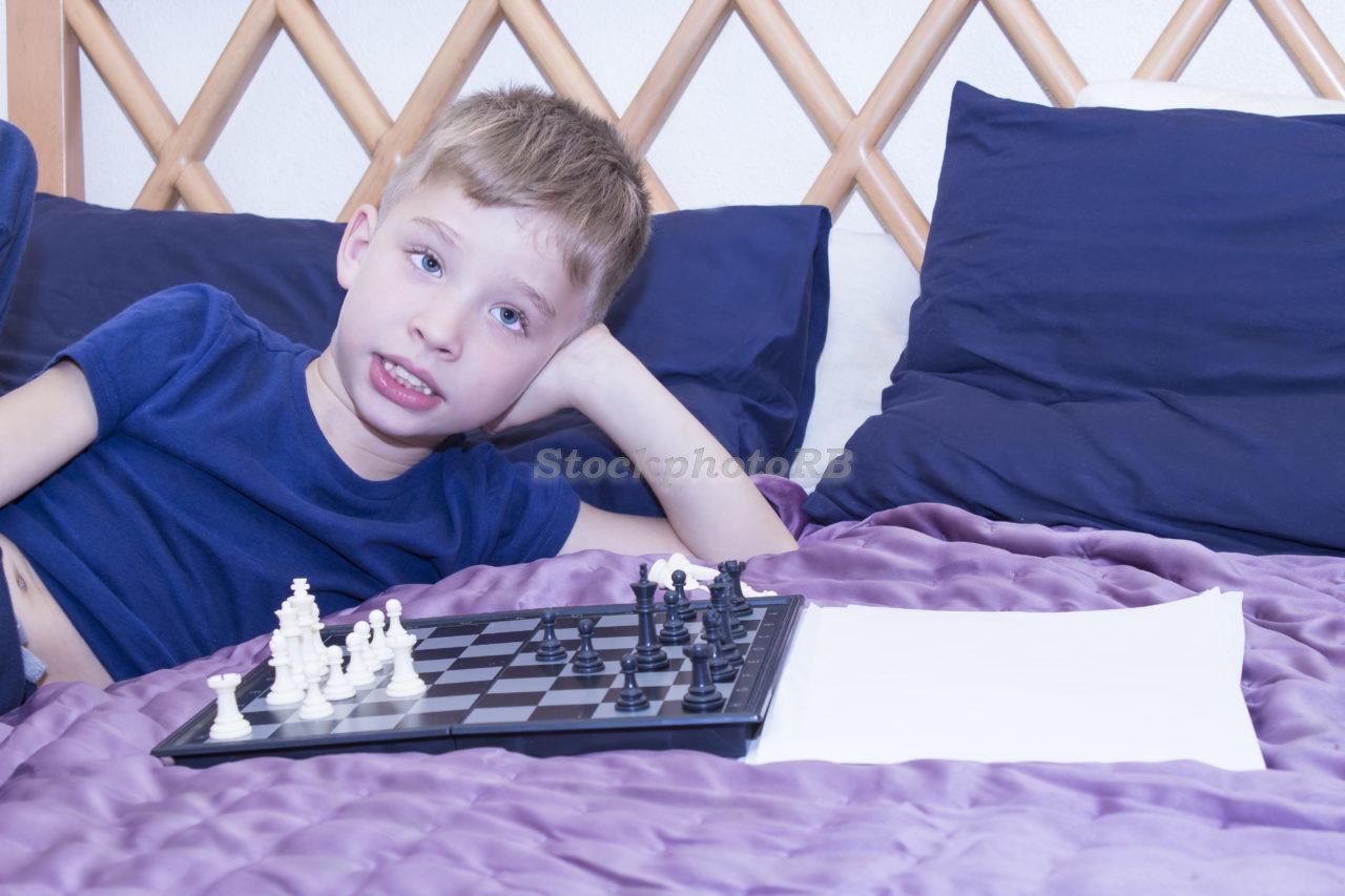 A little boy plays chess